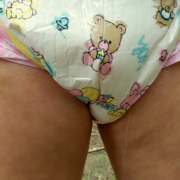 Close-up shot of Alisha peeing in a diaper.