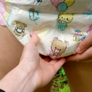 Close-up shot of Alisha feeling Olivia's wet diaper.