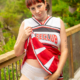 Wearing a cheer uniform, Lola teasingly lifts her skirt showing off her pull-on style diaper.