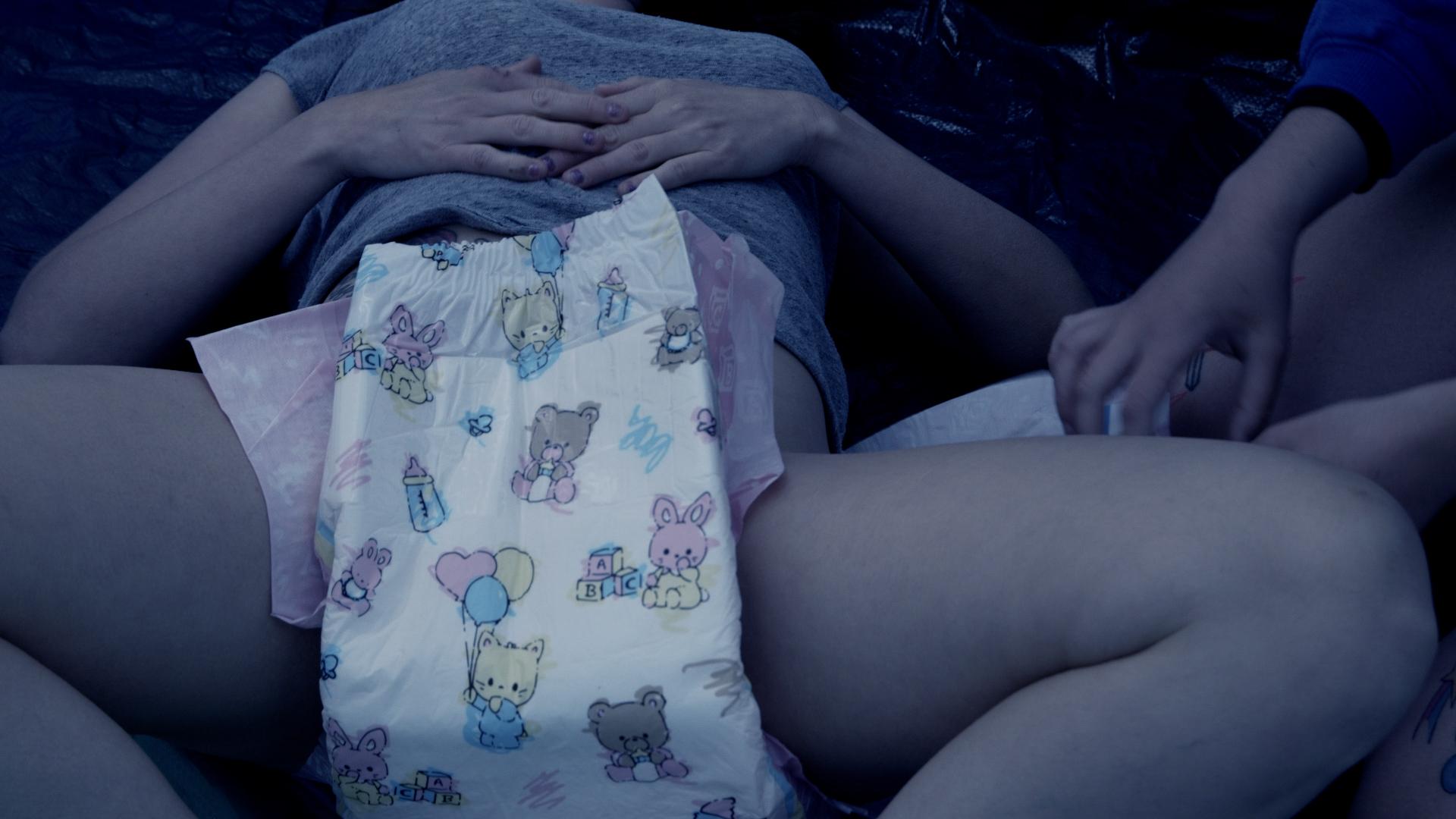 Close-up of Olivia changing Alisha's diaper.