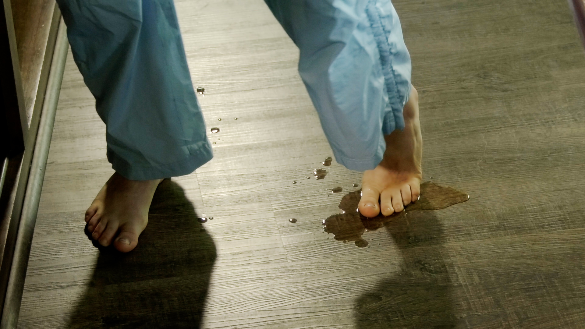 A small puddle forms around Lola's feet as a result of her diaper leaking.
